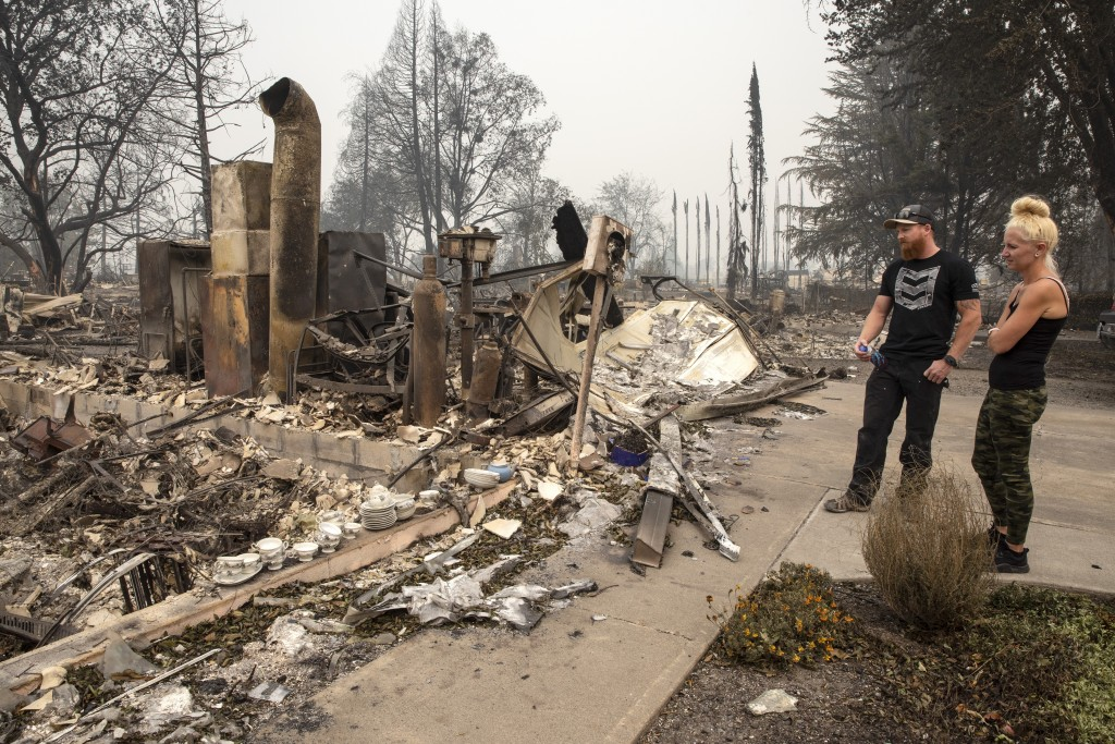 Derek Trenton and Shawna Haptonstall  look at the ruins of Derek's parents home as wildfires devastate the region, Friday, Sept. 11, 2020 in Talent, O...