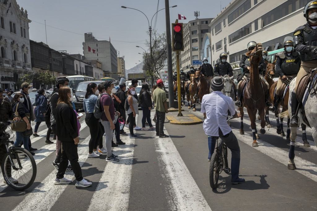 Pedestrians to try to cross Abancay Avenue where mounted police patrol outside Congress in Lima, Peru, Friday, Sept. 11, 2020. Some of Peru's lawmaker...