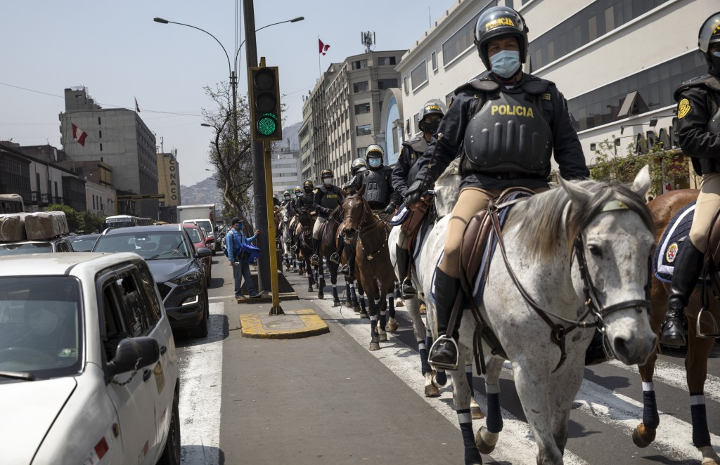 Mounted police patrol outside Congress in Lima, Peru, Friday, Sept. 11, 2020. Some of Peru's lawmakers are calling for the dismissal of President Mart...