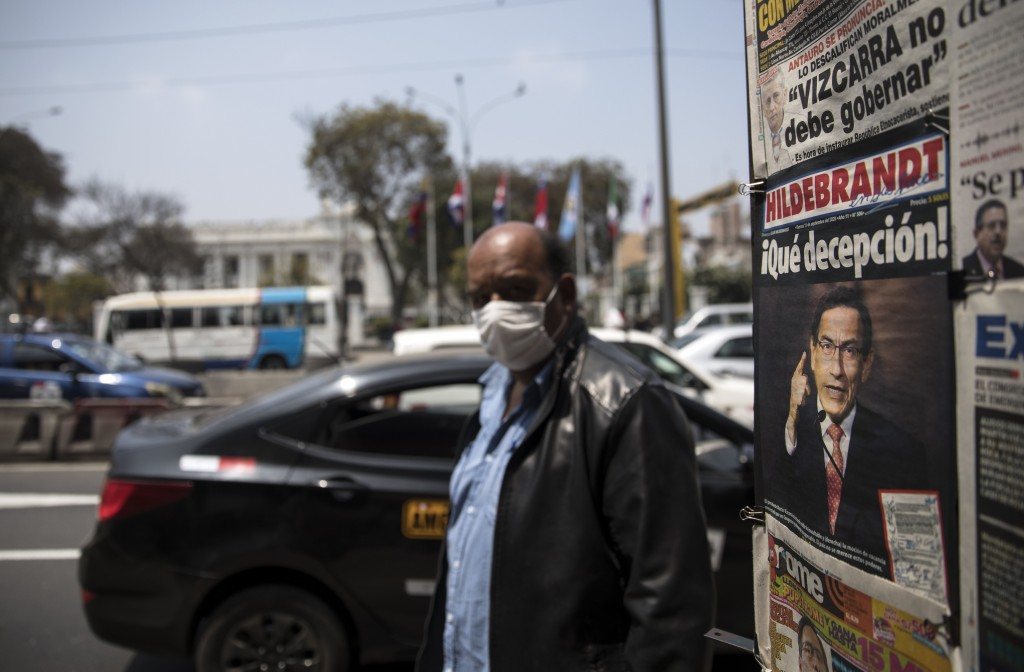 A man wearing a protective face mask due to the COVID-19 pandemic, walks past a newsstand displaying front-page headlines involving Peru's President M...