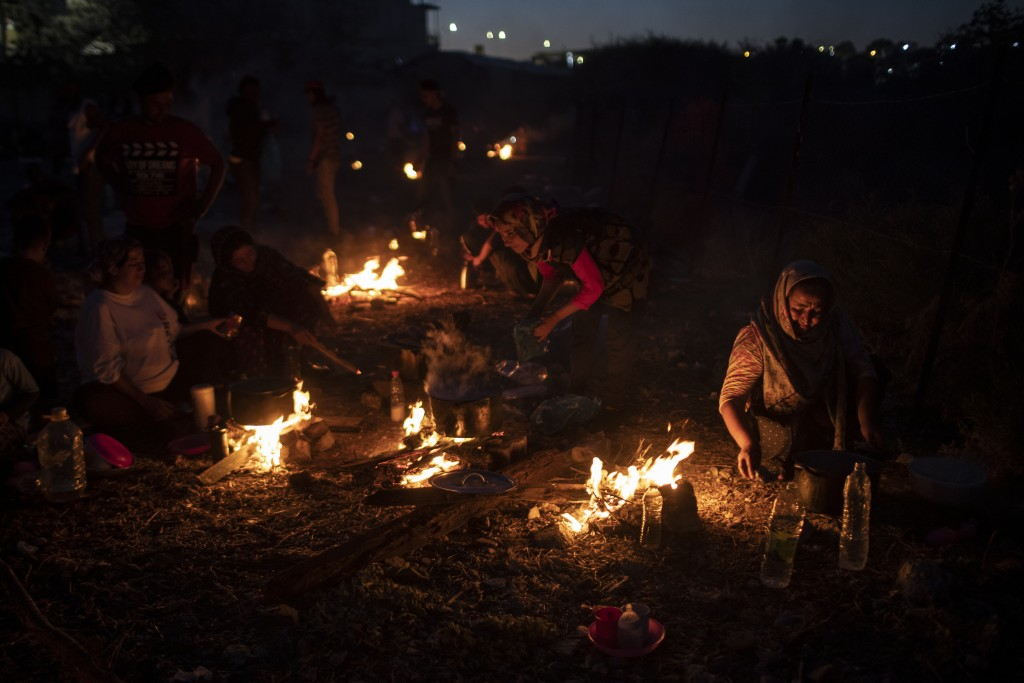 Refugees and migrants cook on makeshift fires near an abandoned factory in the island of Lesbos, Greece, Friday, Sept. 11, 2020. Thousands of refugees...