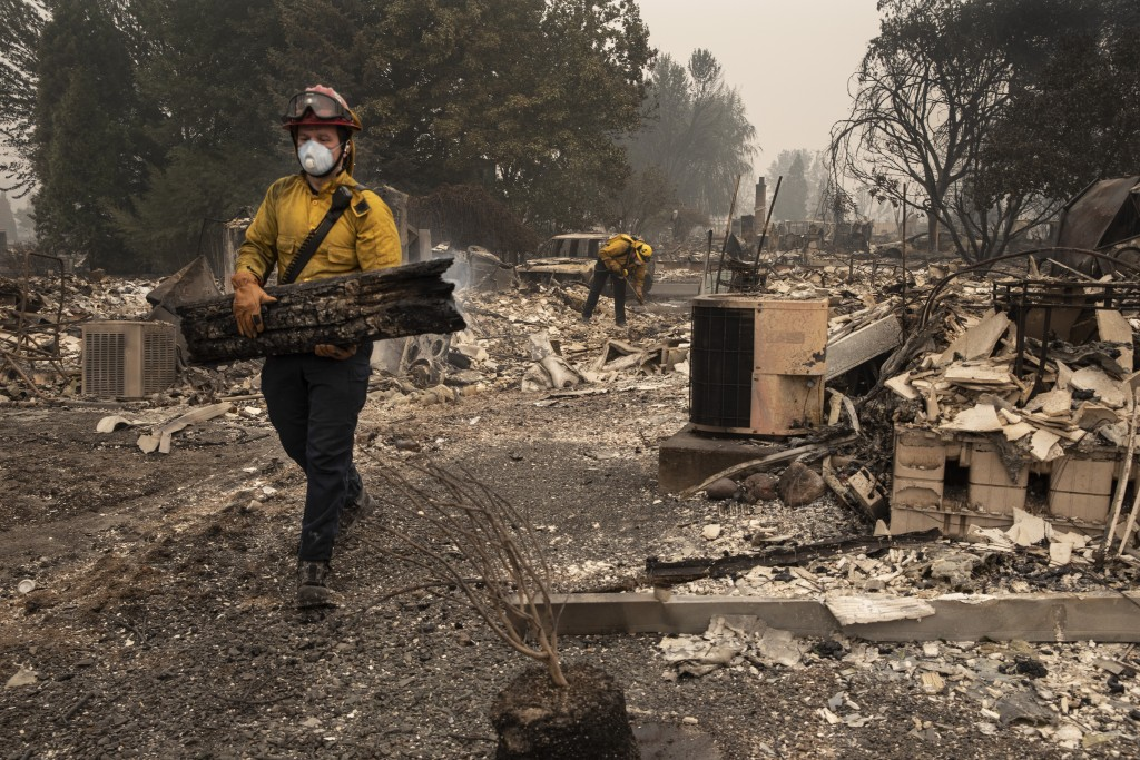 Jackson County District 5 firefighter Captain Aaron Bustard works on a smoldering fire in a burned neighborhood in Talent, Ore., Friday, Sept. 11, 202...