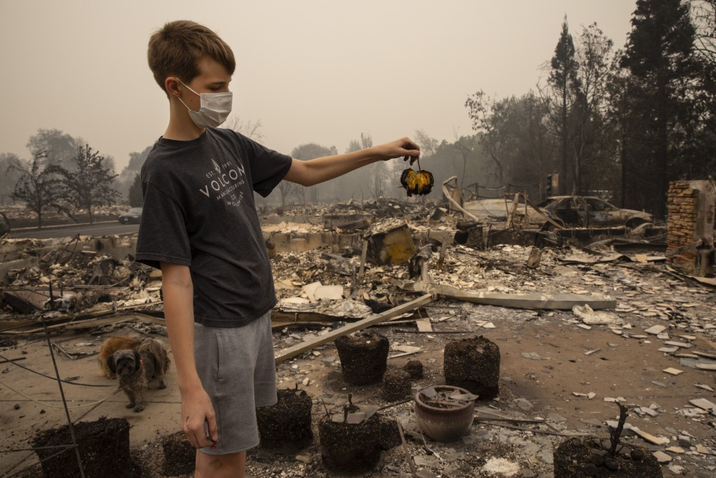 Jacen Sullivan, 14, from Talent, Ore., holds a burned tomato he found in the garden at his burned home in Talent on Friday, Sept. 11, 2020, as destruc...
