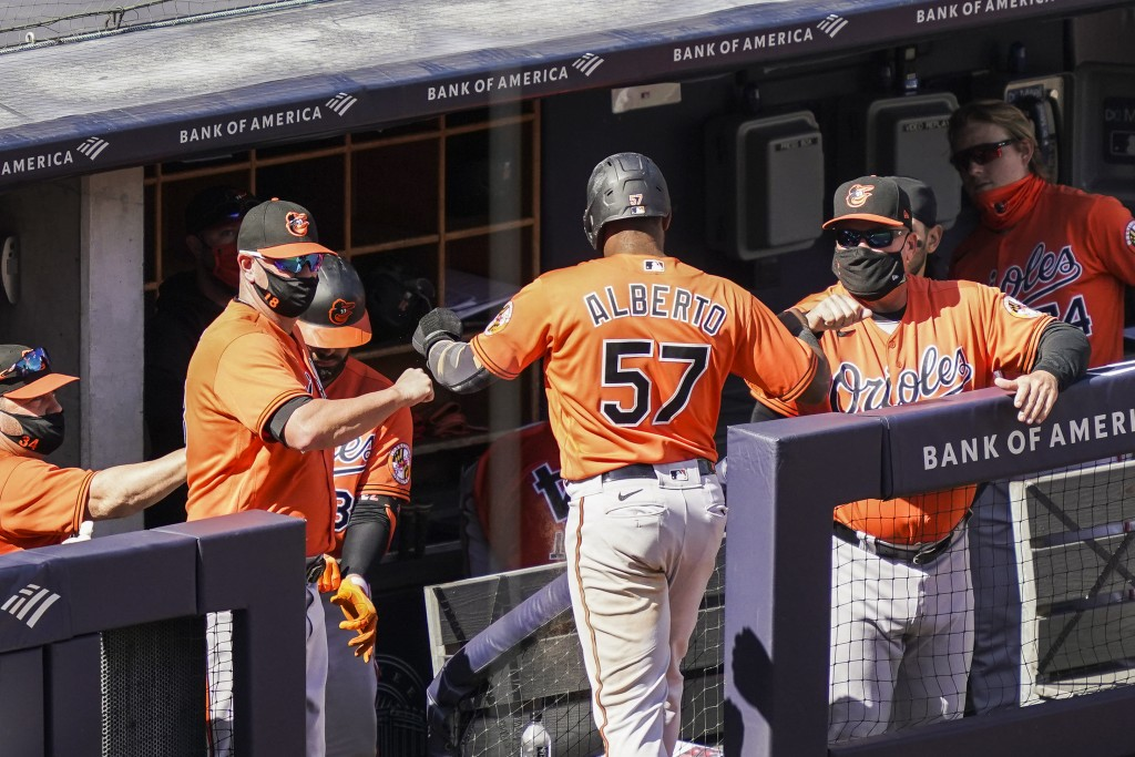 Baltimore Orioles' Hanser Alberto (57) celebrates with staff wearing protective masks after scoring on an RBI single hit by Ryan Mountcastle off New Y...