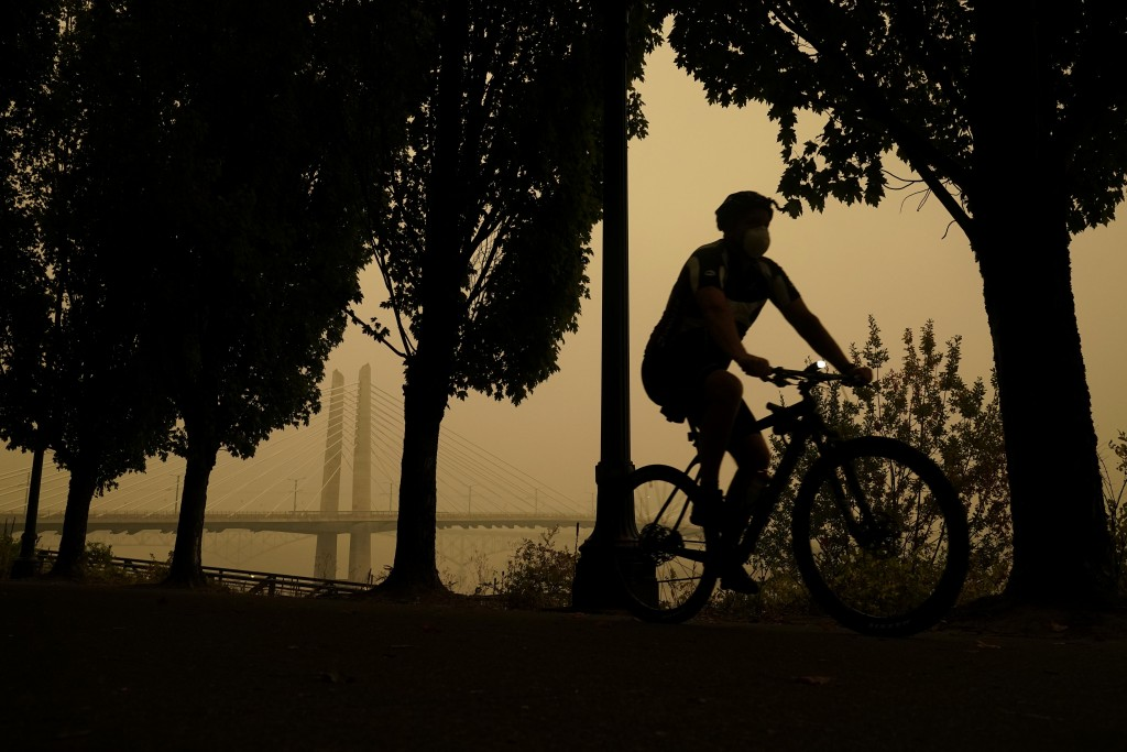 A person rides a bike along the Willamette River as smoke from wildfires partially obscures the Tilikum Crossing Bridge, Saturday, Sept. 12, 2020, in ...