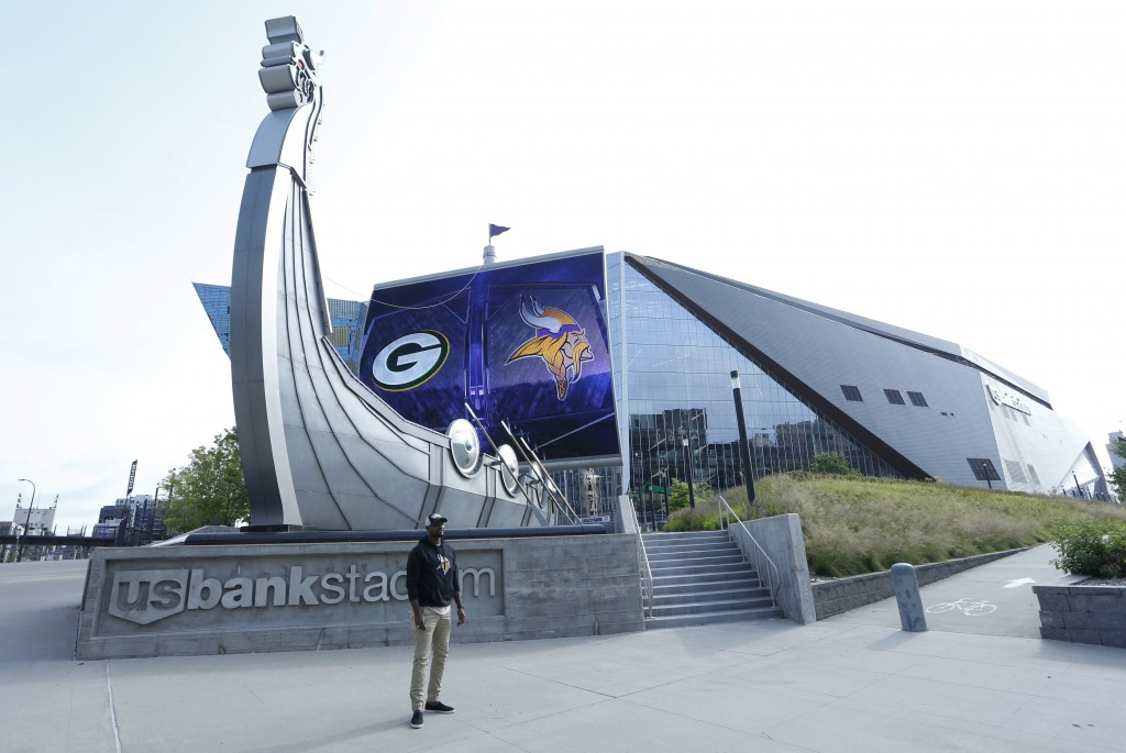 A lone fan has his picture taken in front of U.S. Bank Stadium before an NFL football game between the Minnesota Vikings and the Green Bay Packers, Su...