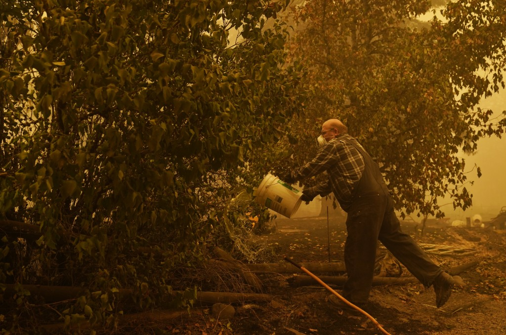 George Coble douses a still smoldering tree at his property destroyed by a wildfire Saturday, Sept. 12, 2020, in Mill City, Ore. (AP Photo/John Locher...