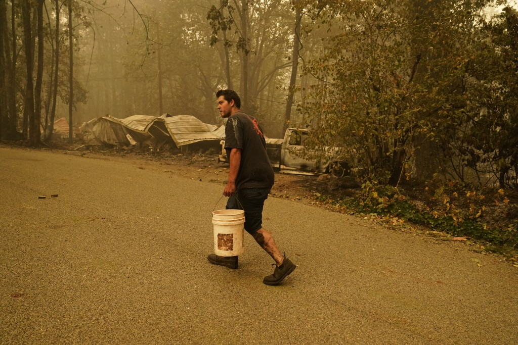 Erik Tucker carries a bucket of water to put out hot spots in an area around his home burned by the Beachie Creek Fire, Saturday, Sept. 12, 2020, in L...