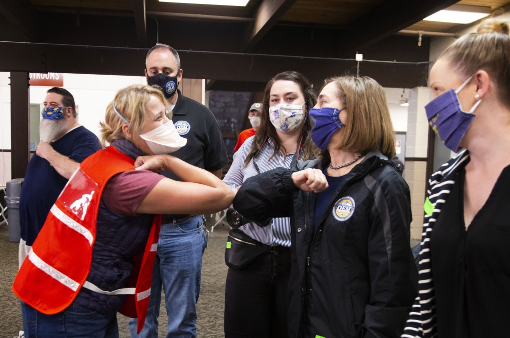 Brenda Pearson, left, Marion County's Emergency Management field branch manager, greets Oregon Governor Kate Brown, second right, before touring her t...