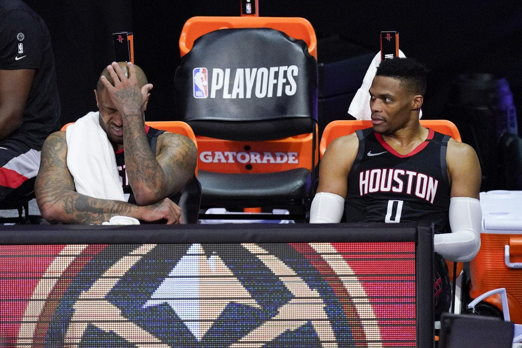 Houston Rockets' P.J. Tucker, left, and Russell Westbrook sit on the bench in the closing minutes of a loss to the Los Angeles Lakers during the secon...