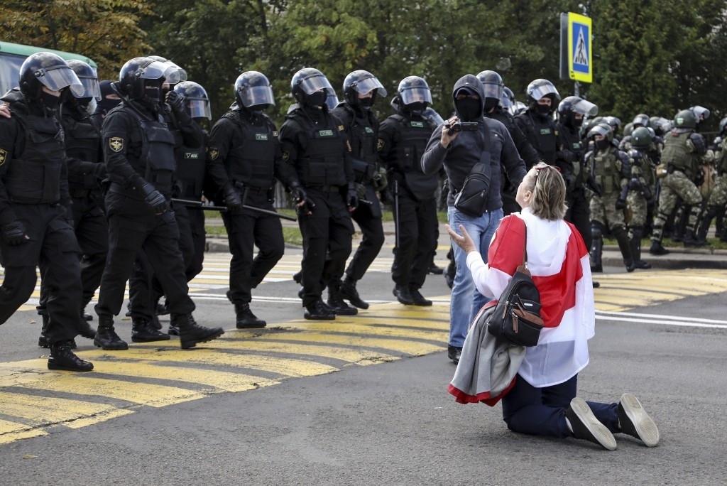 A woman covered herself by an old Belarusian national flag kneels in front of a riot police line as they block Belarusian opposition supporters rally ...