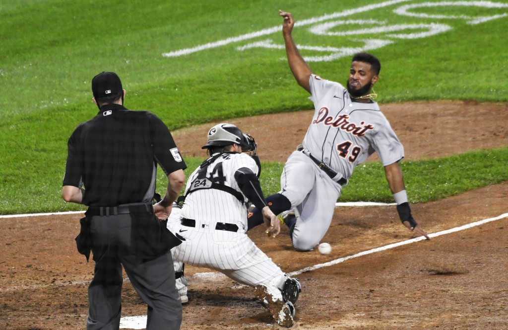 Chicago White Sox catcher Yasmani Grandal (24) prepares to tag Willi Castro (49) out at home plate during the fourth inning of a baseball game, Saturd...