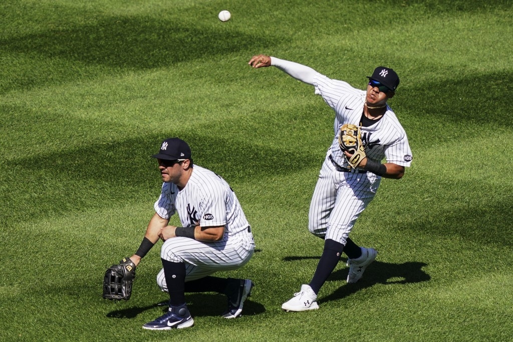 New York Yankees second baseman Thairo Estrada, right, throws towards home plate after a ball dropped for an RBI single by Baltimore Orioles' Ryan Mou...