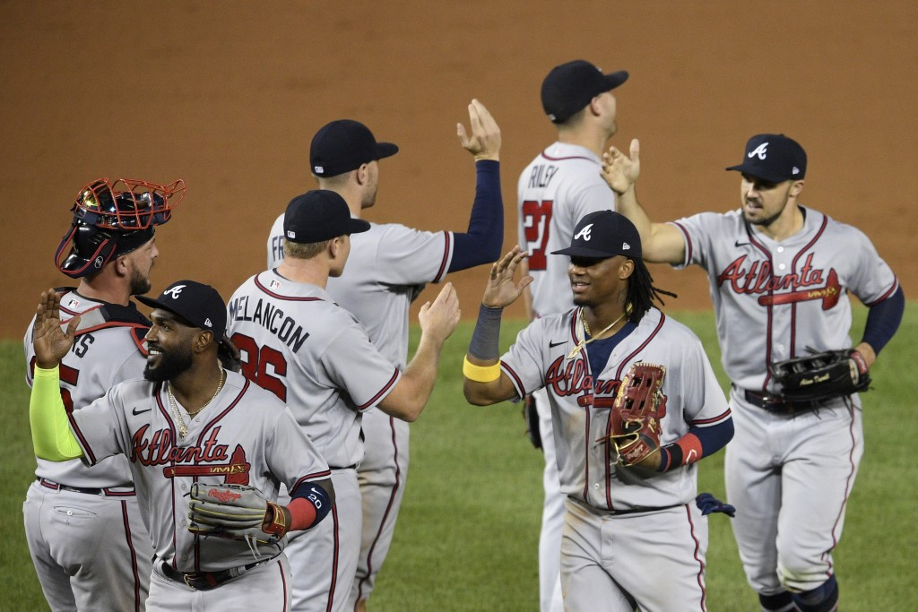 Atlanta Braves' Marcell Ozuna, front left, Ronald Acuna Jr., front center, Adam Duvall, front right, and others celebrate after a baseball game agains...