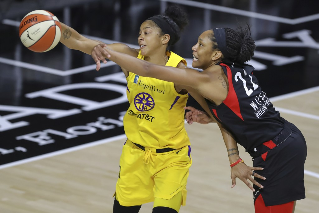 Las Vegas Aces' A'ja Wilson (22) reaches to deflect a pass intended for Los Angeles Sparks' Candace Parker during the first half of a WNBA basketball ...