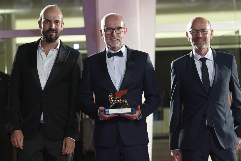 "Disney's Marketing Director for Italy, Davide Romani, center, holds the Golden Lion Best Film award for ""Nomadland"", at the closing ceremony of 77th e..."