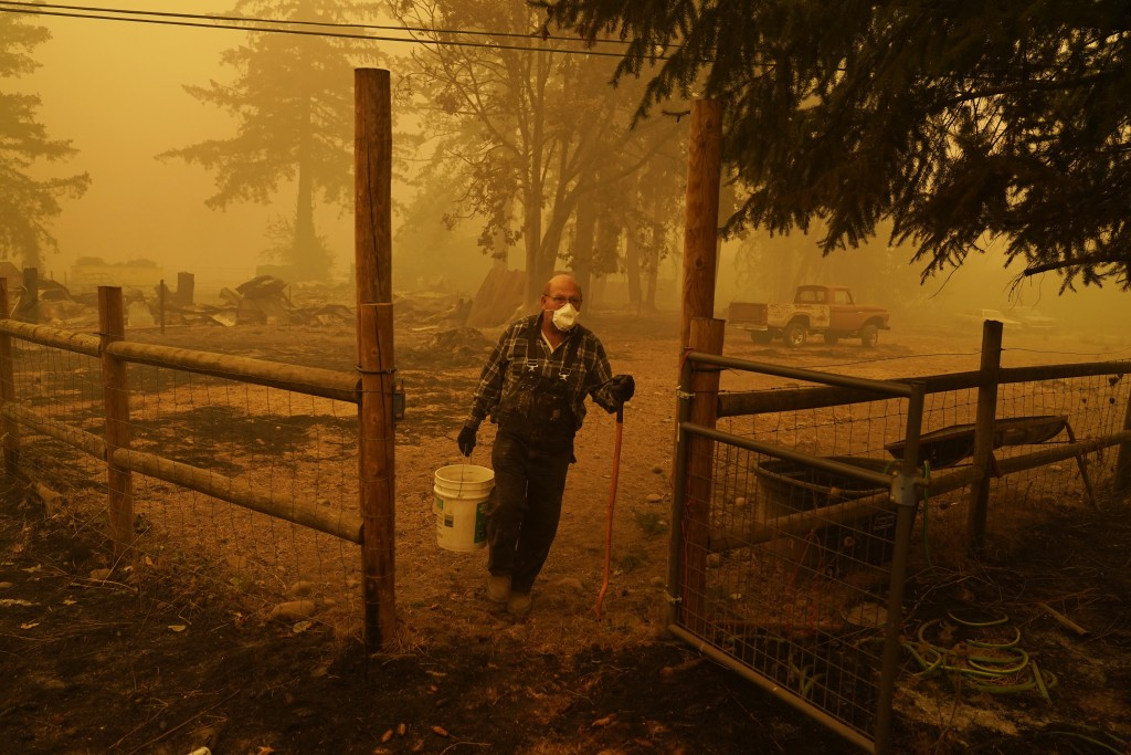 George Coble carries a bucket of water to put out a tree still smoldering on his property destroyed by a wildfire Saturday, Sept. 12, 2020, in Mill Ci...