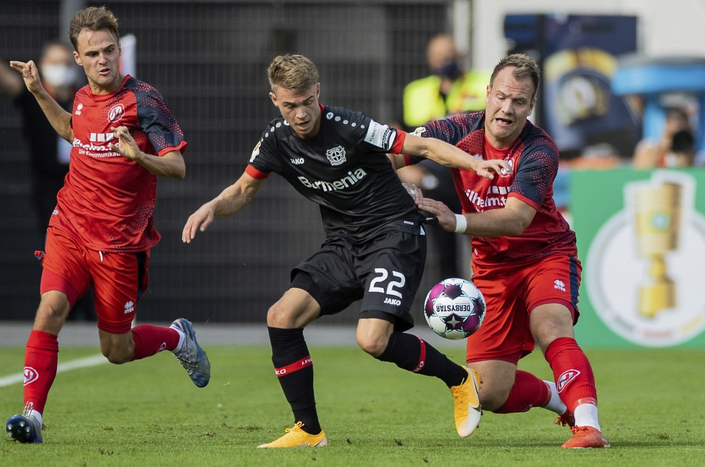 Leverkusen's Daley Sinkgraven, center, and Norderstedt' Jan Lueneburg, right, challenge for the ball during the German Soccer Cup first round match be...