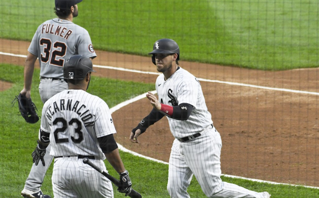 Chicago White Sox's Yasmani Grandal, right, is greeted by Edwin Encarnacion, left, after scoring against the Detroit Tigers during the first inning of...