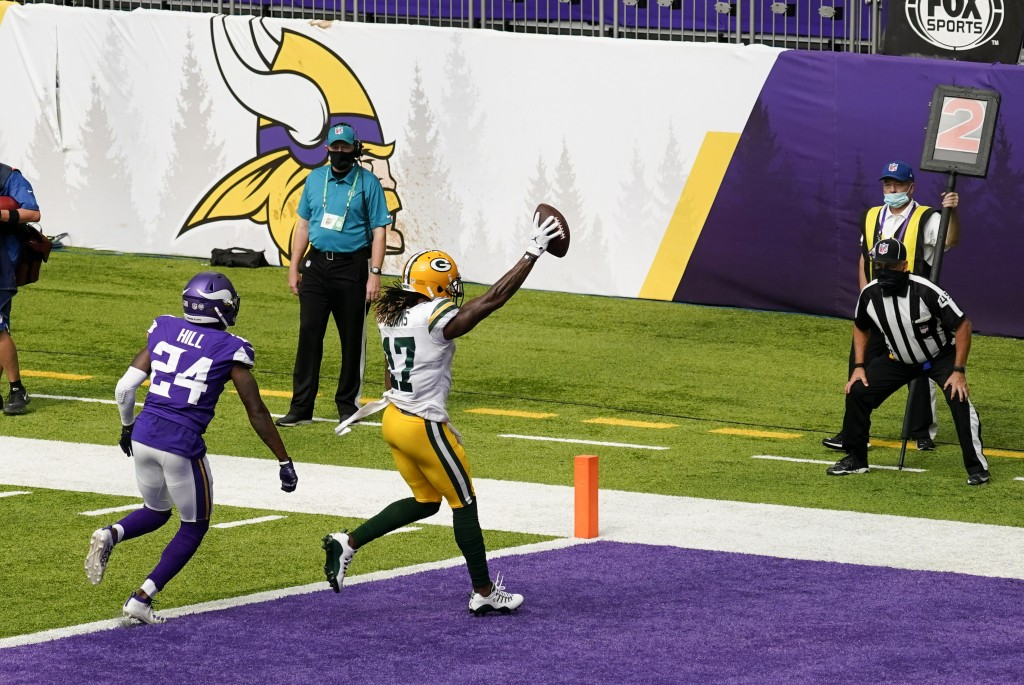 Green Bay Packers wide receiver Davante Adams (17) catches a 1-yard touchdown pass ahead of Minnesota Vikings defensive back Holton Hill (24) during t...