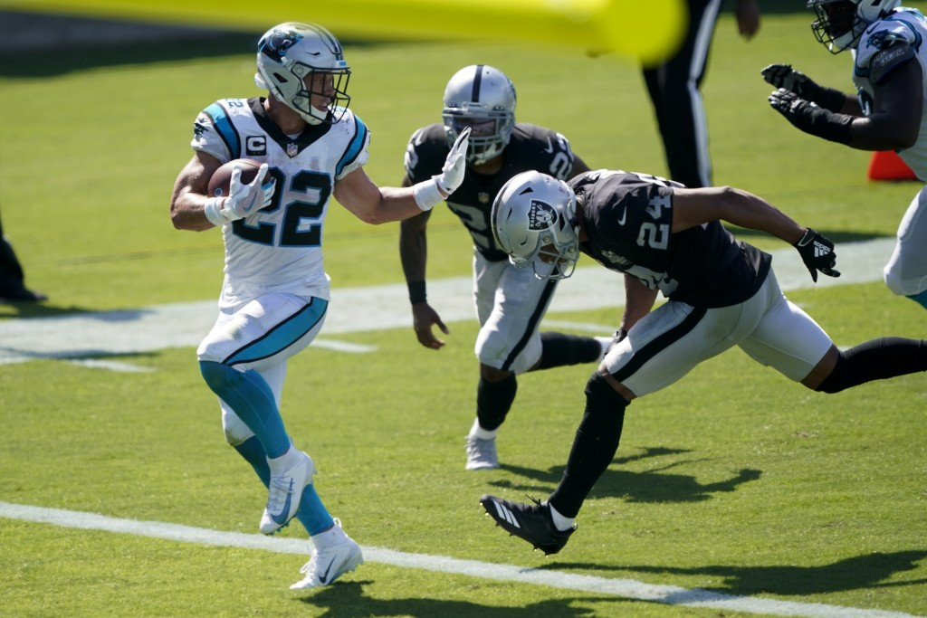 Carolina Panthers running back Christian McCaffrey scores ahead of Las Vegas Raiders safety Johnathan Abram during the second half of an NFL football ...