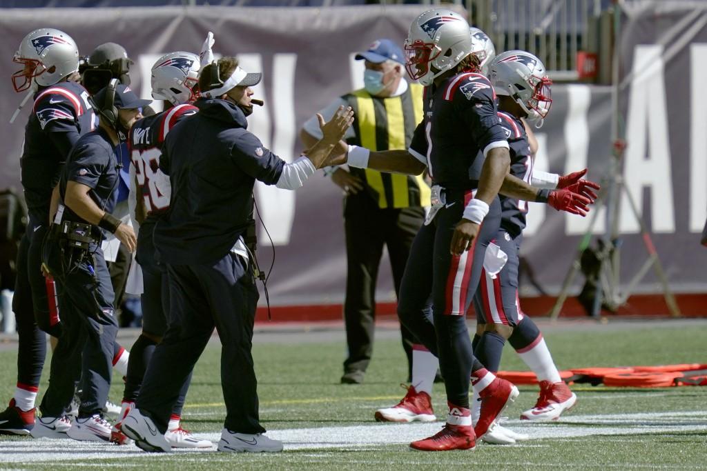 New England Patriots offensive coordinator Josh McDaniels, left, congratulates quarterback Cam Newton on his second rushing touchdown against the Miam...