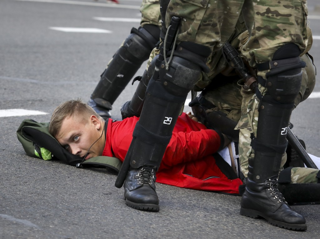 Riot police officers detain a protester during a Belarusian opposition supporters' rally protesting the official presidential election results in Mins...