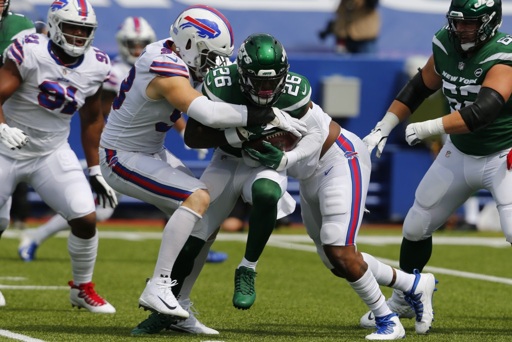New York Jets running back Le'Veon Bell (26) is stopped by Buffalo Bills defensive ends Trent Murphy, center left, and Quinton Jefferson, center right...