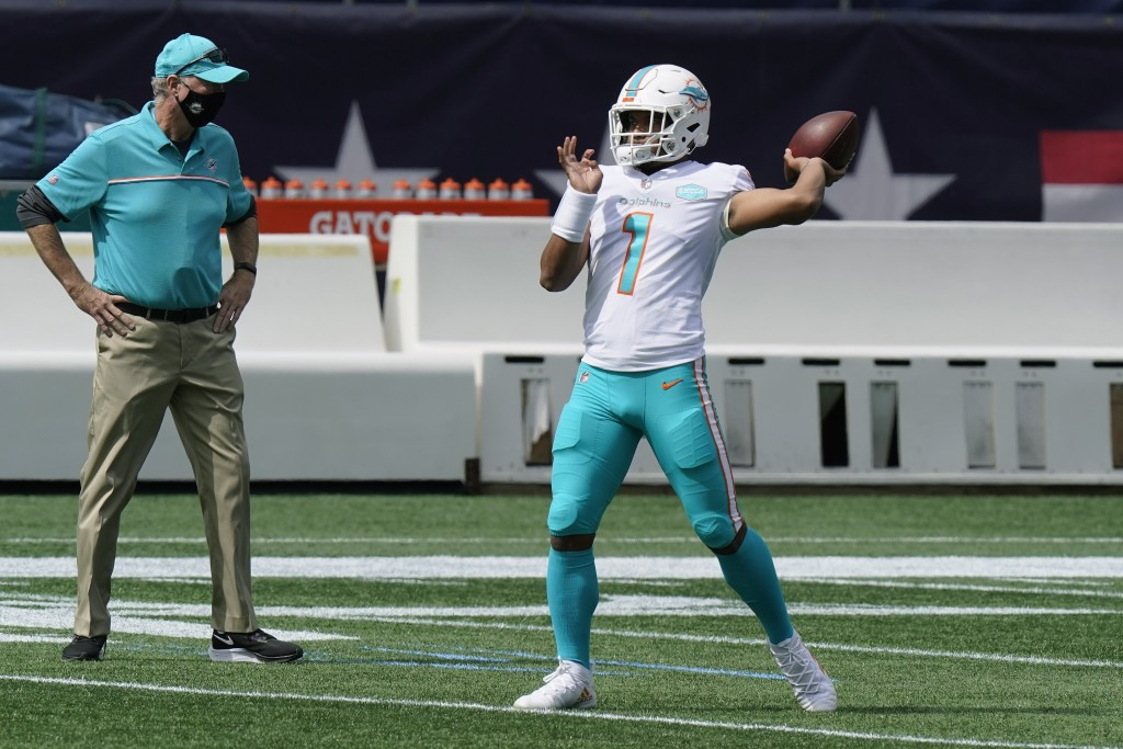 FILE - Miami Dolphins quarterback Tua Tagovailoa warms up before an NFL football game against the New England Patriots, Sunday, Sept. 13, 2020, in Fox...