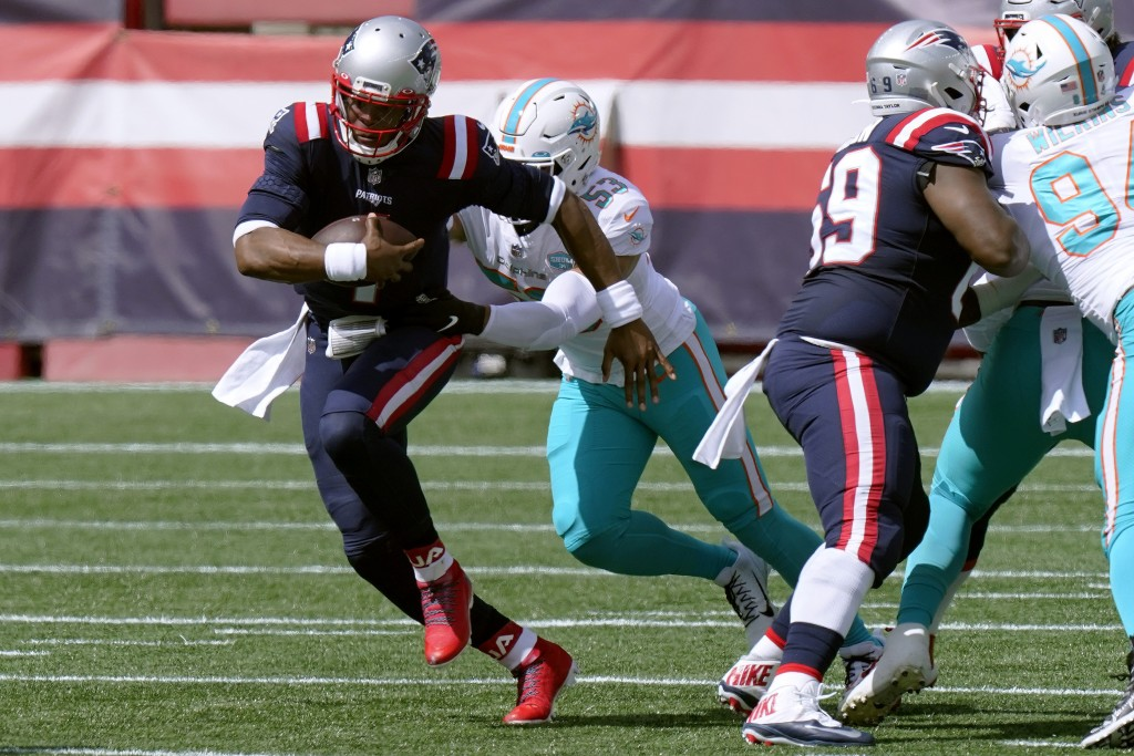 New England Patriots quarterback Cam Newton, front, runs from Miami Dolphins linebacker Kyle Van Noy (53)in the first half of an NFL football game, Su...