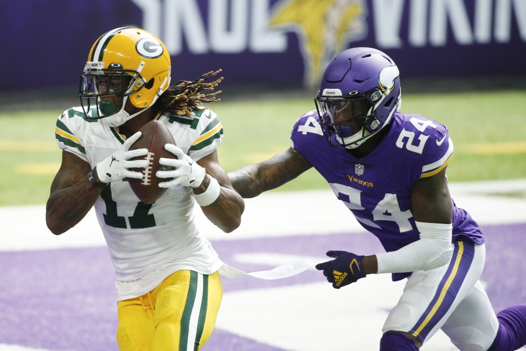 Green Bay Packers wide receiver Davante Adams catches a 1-yard touchdown pass ahead of Minnesota Vikings defensive back Holton Hill, right, during the...