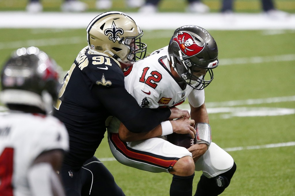 Tampa Bay Buccaneers quarterback Tom Brady (12) is sacked by New Orleans Saints defensive end Trey Hendrickson (91) in the first half of an NFL footba...