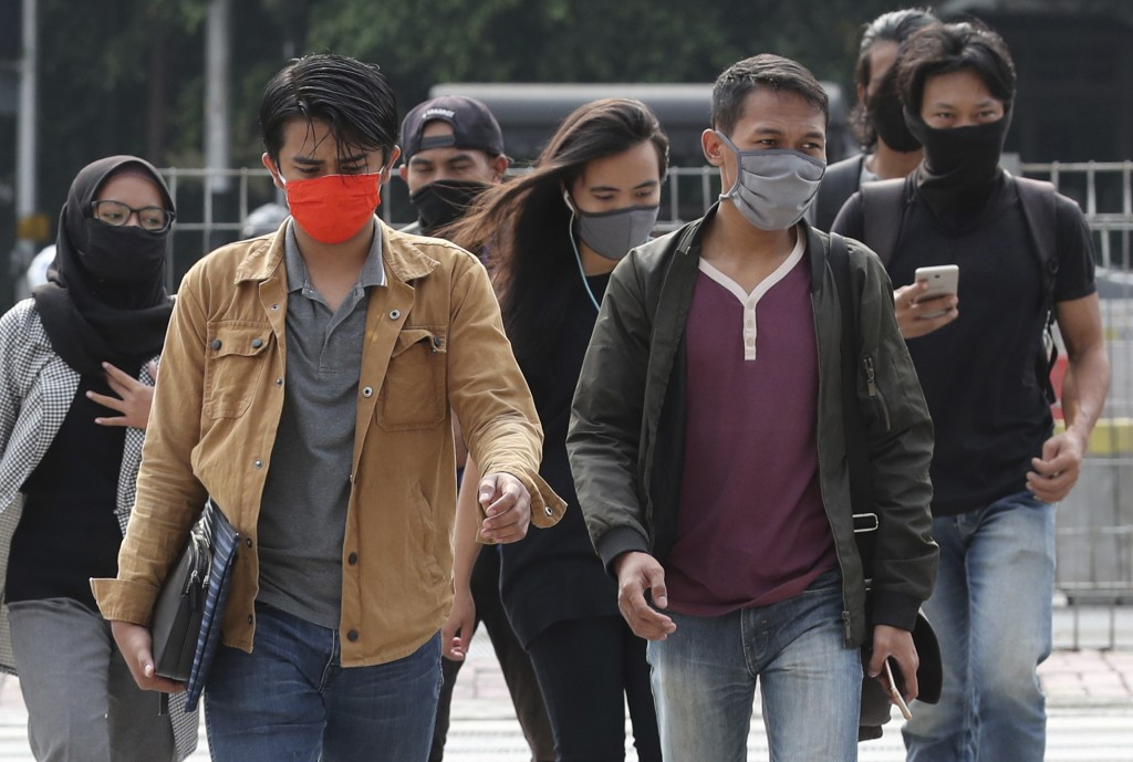 People, wearing a face mask as a precaution against the new coronavirus outbreak, walk on a pedestrian crossing at the main business district in Jakar...