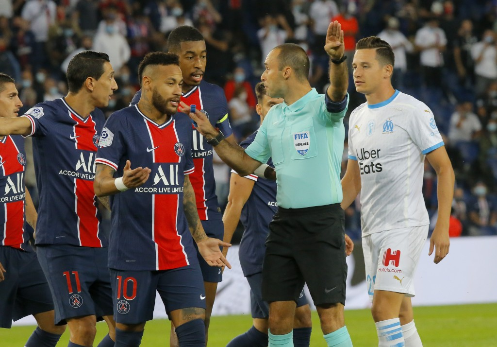 Referee Jerome Brisard waves away the appeals of PSG players for a penalty during the French League One soccer match between Paris Saint-Germain and M...
