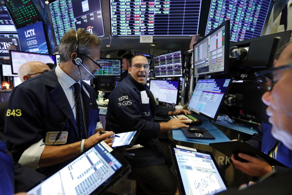 FILE - In this Aug. 21, 2019, file photo, specialist Anthony Matesic, center, works with traders at his post on the floor of the New York Stock Exchan...