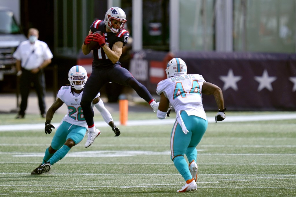 New England Patriots wide receiver Julian Edelman (11) attempts to catch a pass between Miami Dolphins safety Bobby McCain (28) and linebacker Elandon...