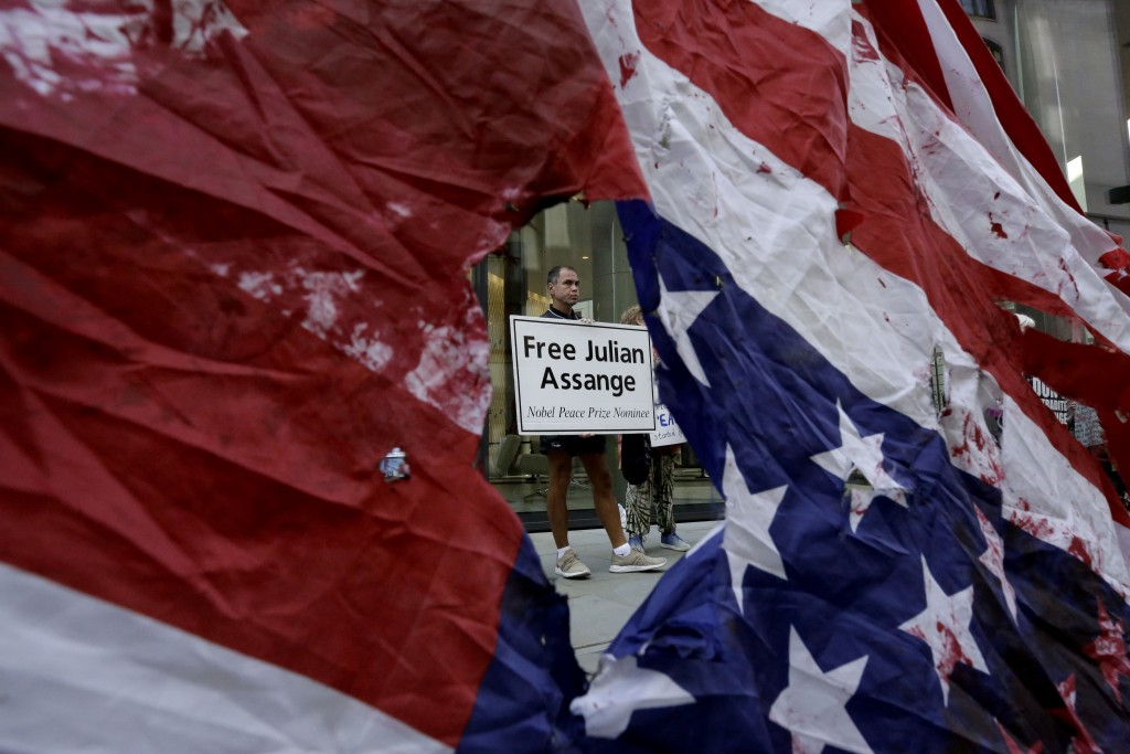 A supporter of WikiLeaks founder Julian Assange is seen through a hole torn in a defaced U.S. flag during a protest outside the Central Criminal Court...