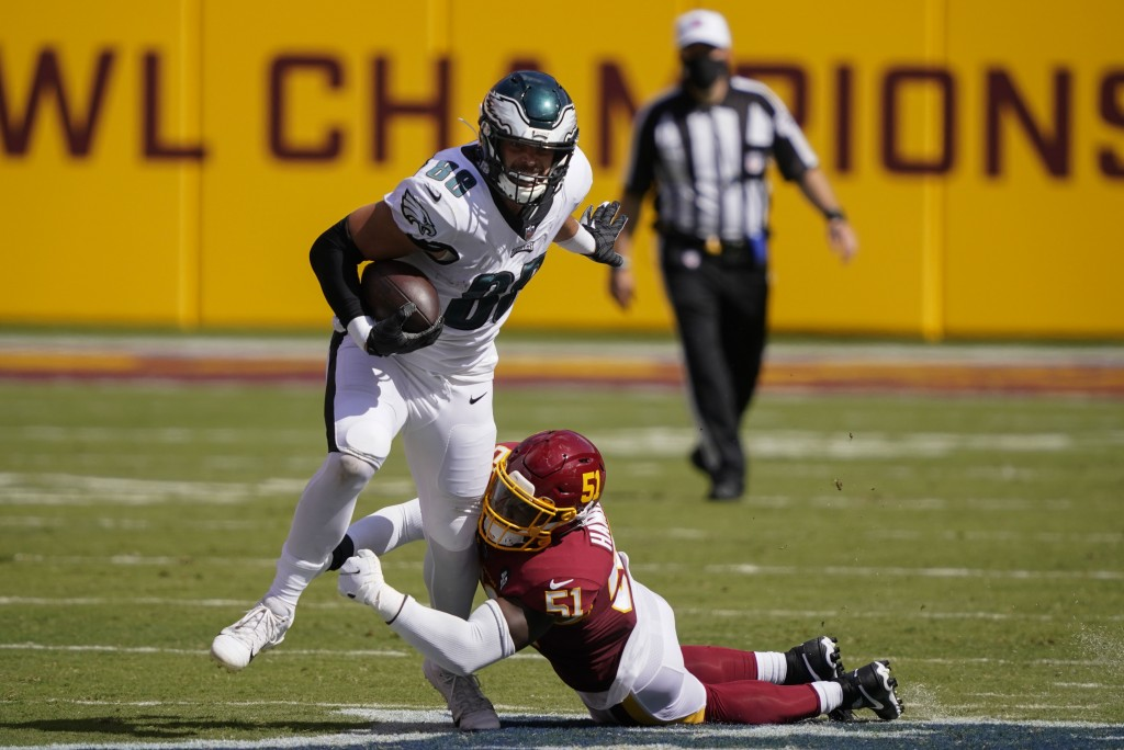 Philadelphia Eagles tight end Dallas Goedert (88) tries to break away from a tackle by Washington Football Team linebacker Shaun Dion Hamilton (51) du...