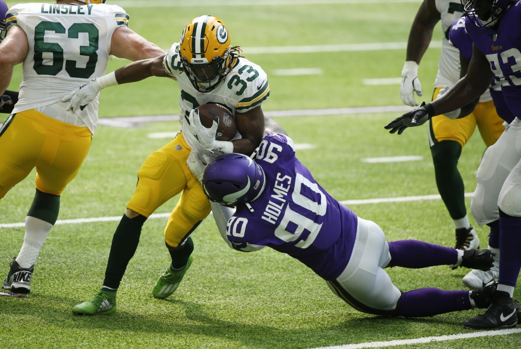 Green Bay Packers running back Aaron Jones (33) tries to break a tackle by Minnesota Vikings defensive tackle Jalyn Holmes during the first half of an...