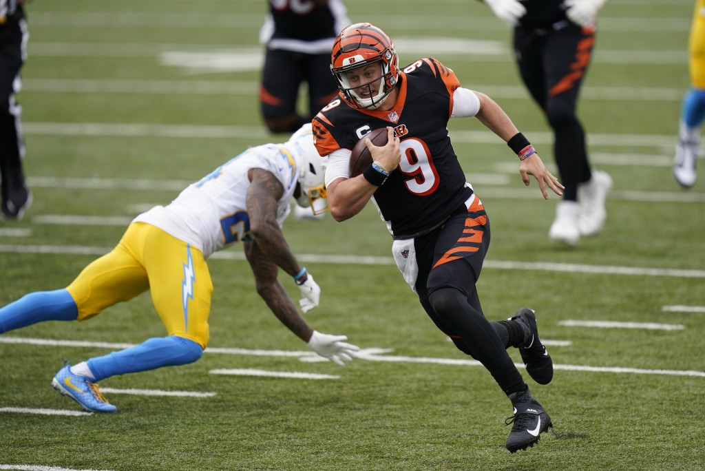 Cincinnati Bengals quarterback Joe Burrow (9) runs past Los Angeles Chargers' Rayshawn Jenkins (23) for a touchdown during the first half of an NFL fo...