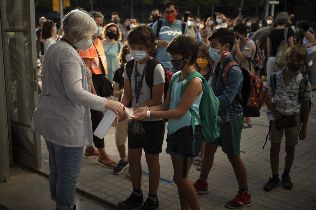 Students wearing face masks to prevent the spread of coronavirus disinfect their hands before entering their school in Barcelona, Spain, Monday, Sept....