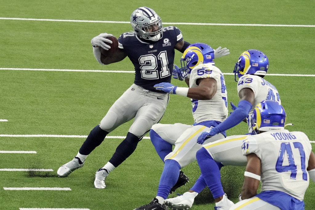 Dallas Cowboys' Ezekiel Elliott (21) runs around a group of Los Angeles Rams defenders on his way to a touchdown after a catch during the first half o...