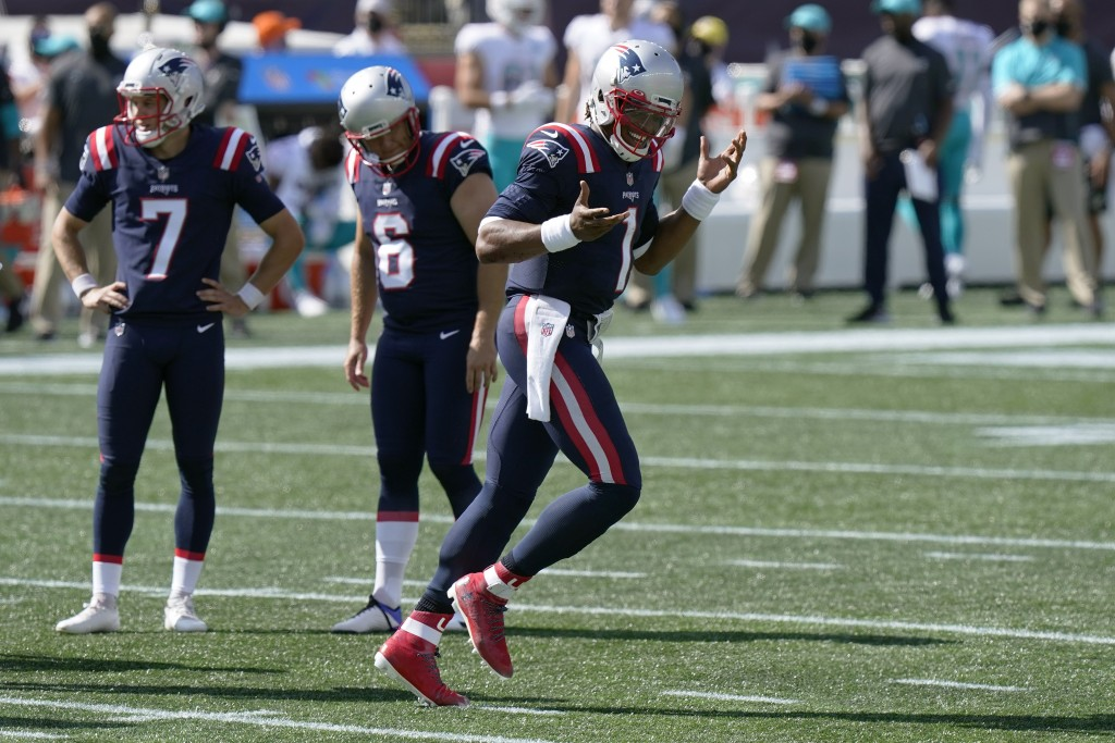 New England Patriots quarterback Cam Newton, right, celebrates his second rushing touchdown as he heads to the bench in the second half of an NFL foot...