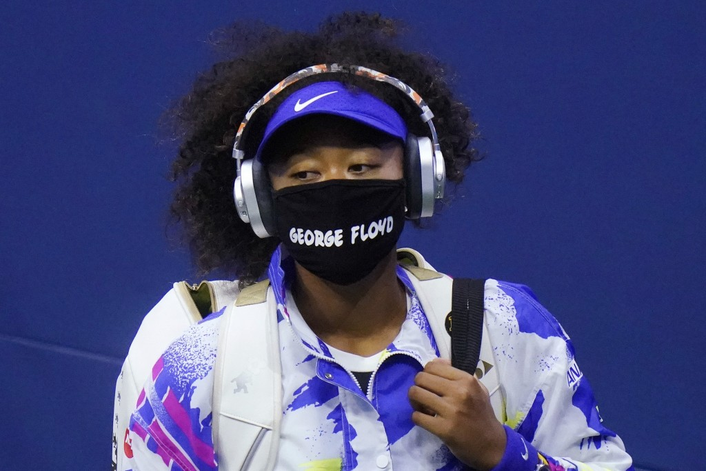 """FILE - In this Sept. 8, 2020, file photo, Naomi Osaka, of Japan, wears a protective mask due to the COVID-19 virus outbreak, featuring the name """"Georg..."""