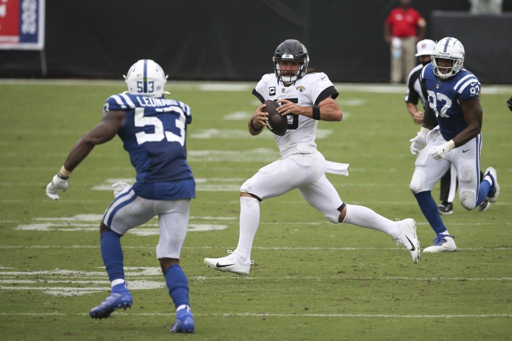 Jacksonville Jaguars quarterback Gardner Minshew, center, scrambles for yardage between Indianapolis Colts outside linebacker Darius Leonard (53) and ...