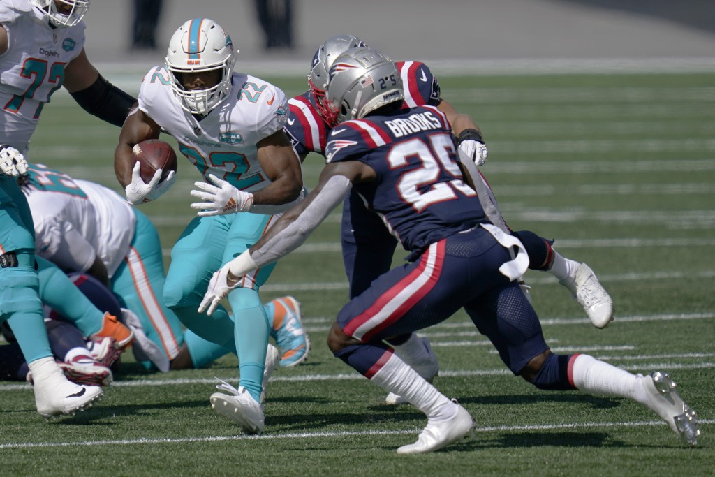 Miami Dolphins running back Matt Breida (22) carries the ball as New England Patriots defensive back Terrence Brooks (25) chases in the first half of ...