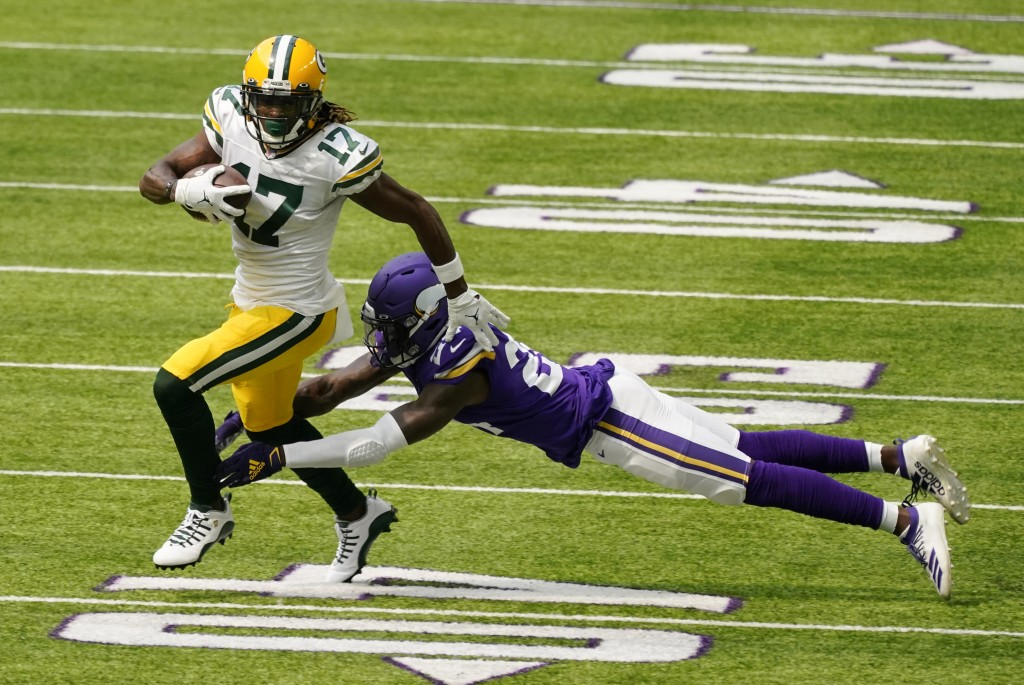 Green Bay Packers wide receiver Davante Adams breaks a tackle by Minnesota Vikings defensive back Holton Hill (24) during the first half of an NFL foo...