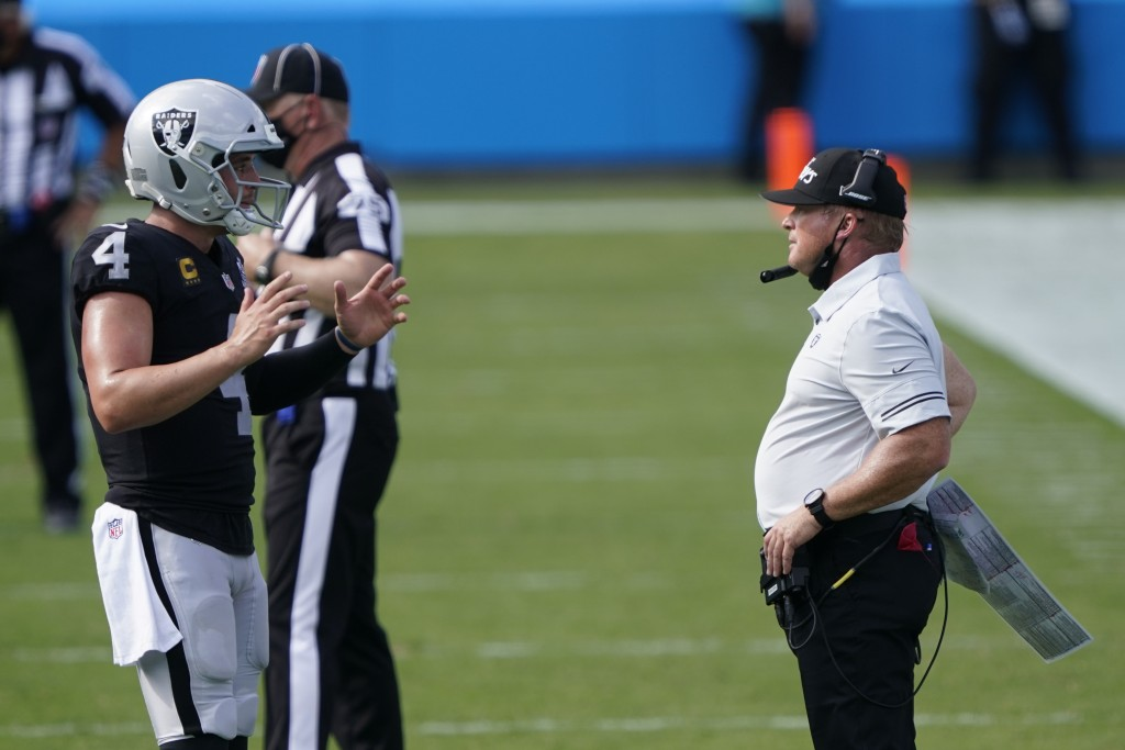 Las Vegas Raiders head coach Jon Gruden talks with quarterback Derek Carr during the second half of an NFL football game against the Carolina Panthers...