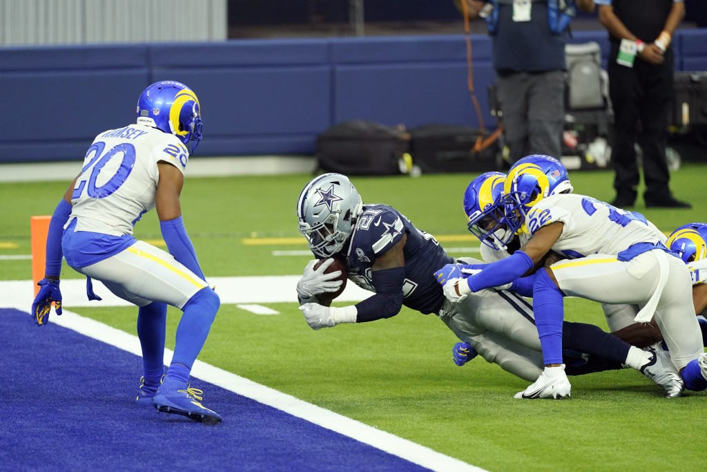 Dallas Cowboys running back Ezekiel Elliott center, scores a touchdown against the Los Angeles Rams during the first half of an NFL football game Sund...