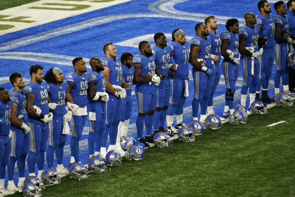 Detroit Lions players stand arm in arm during a social justice video before an NFL football game against the Chicago Bears in Detroit, Sunday, Sept. 1...